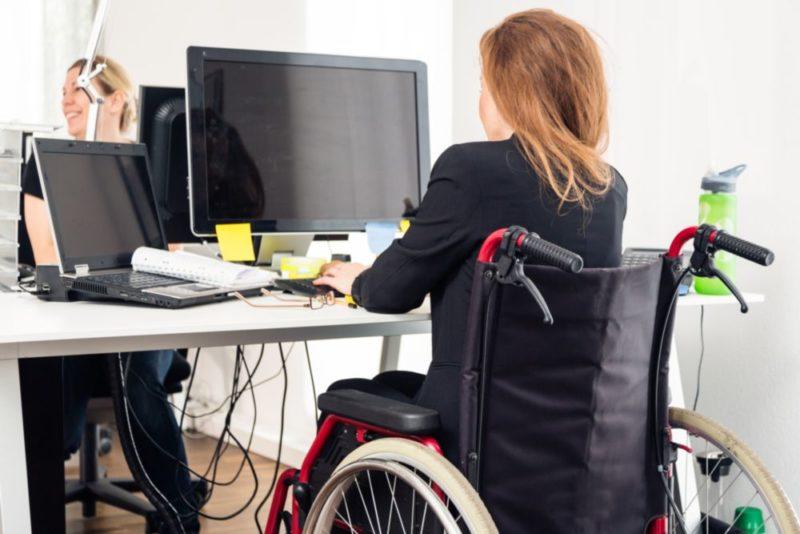 Eine Frau im Rollstuhl sitzt vor einem Computer und links neben ihr steht ein Laptop