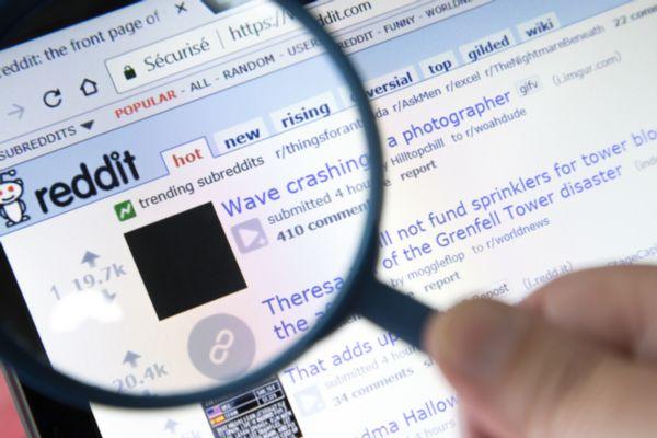 Eine Hand hält eine Lupe, die einen Teil einer Webseite vergrößert