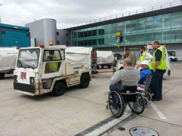Markus und zwei andere Menschen mit Behinderung und das Personal vom Flughafen Manchester warten auf den Einstieg ins Flugzeug in Manchester