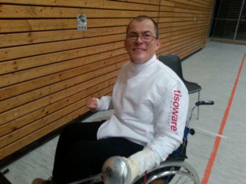 Rollstuhlfechter Markus Lemcke mit Fechtanzug und Degen im Rollstuhl sitzend