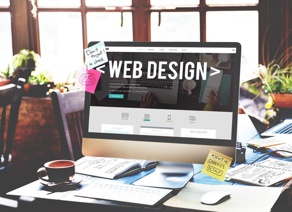 Ein Schreibtisch auf dem ein Monitor steht. Auf dem Monitor steht das Wort Webdesign
